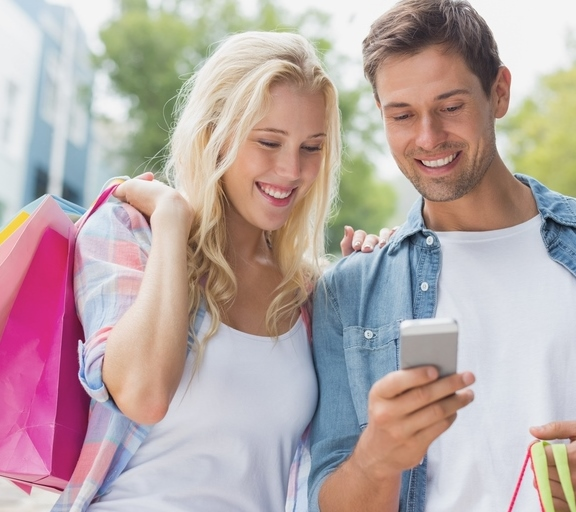 Hip young couple looking at smartphone on shopping trip on a sunny day in the city